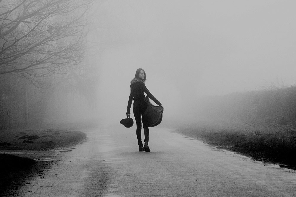 Girl going riding on a misty morning