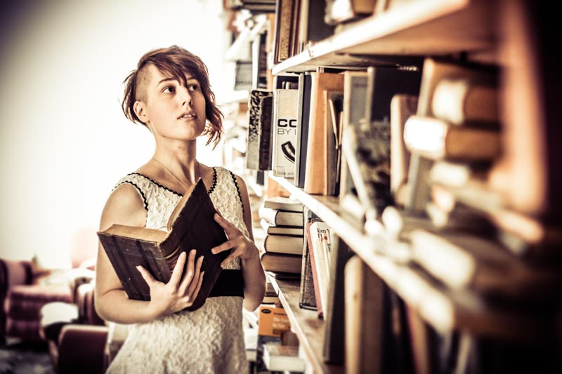 Catherine choosing books from a shelf in an old bookshop